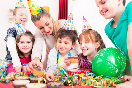 Children at birthday party with muffins and cake